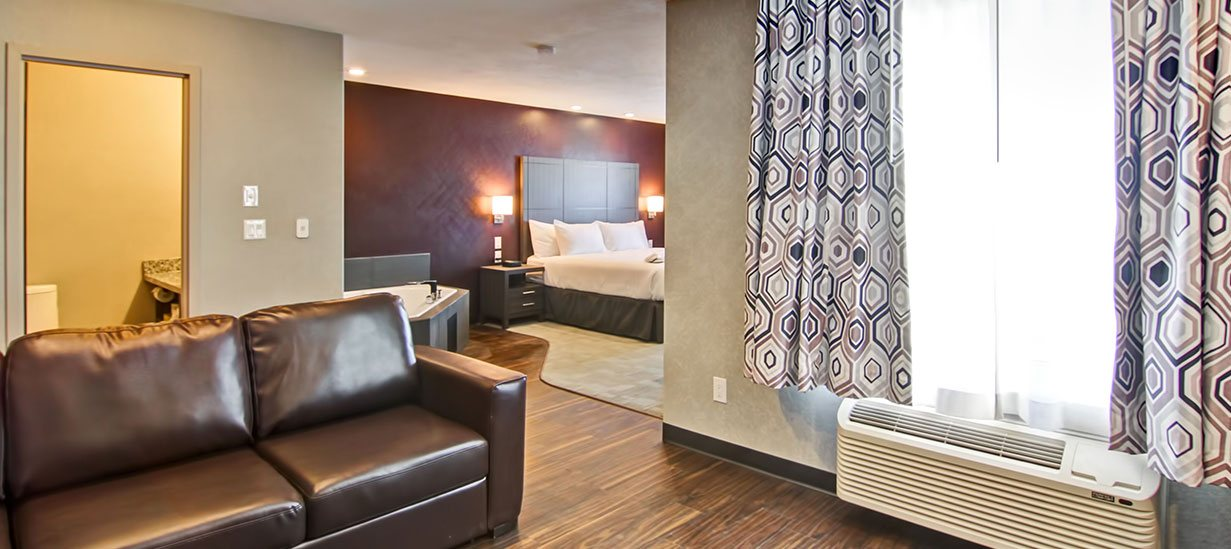 The Jacuzzi Room at d3h Home Inn & Suites Saskatoon South showcases a hot tub placed next to a king sized bed and an accompanying chocolate brown wood beside table.  A dark brown leather loveseat is placed next to an air conditioning unit and a window draped with geometric print curtains.