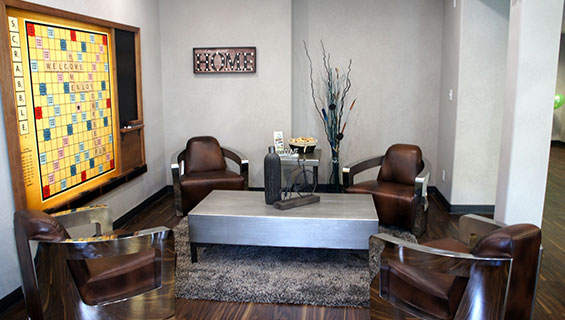 Four leather club chairs encircle a heavy steel top rectangular coffeetable placed over an area rug in the guest lounge area at Home Inn Express in Medicine Hat, Alberta.  A large scrabble board hangs over a white-gray wall, with an attached black chalkboard for keeping score.
