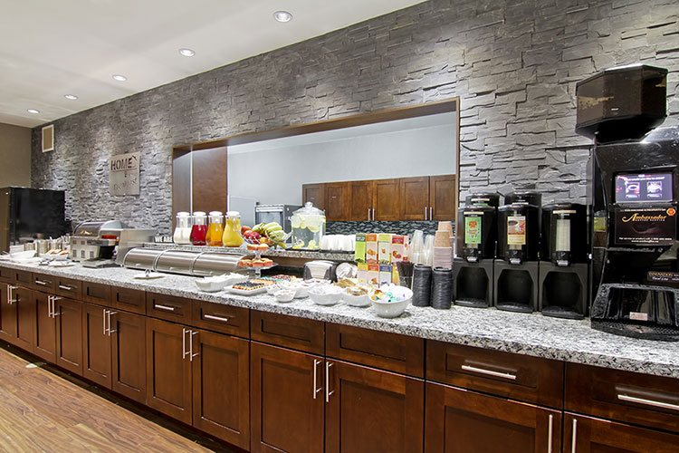 The HomeEssentials breakfast area, offering complimentary breakfast for guests staying at d3h Home Inn & Suites hotels, features a long granite top breakfast bar bearing, pitchers of juice, fruit, baked goods, and amenities such as countertop food warmers, beverage dispensers, and toasters.