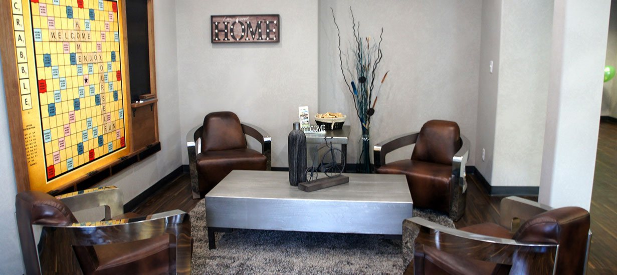 The lounging area at the d3h Home Inn Express in Medicine Hat, Alberta, is furnished with a heavy steel top coffee table surrounded by four brown leather seat club chairs set against the backdrop of a large wall hanging of a Scrabble game board with attached chalkboard.  A matching steel top end table bearing a silver ornamental Welcome sign sits at the periphery of the space.