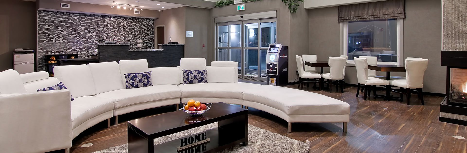 The lobby of the d3h Home Inn & Suites Regina Airport features a bright white curved sectional sofa with decorative purple accent pillows contrasted against the black and white pattern accent wall and charcoal gray stone check in counter in the background.