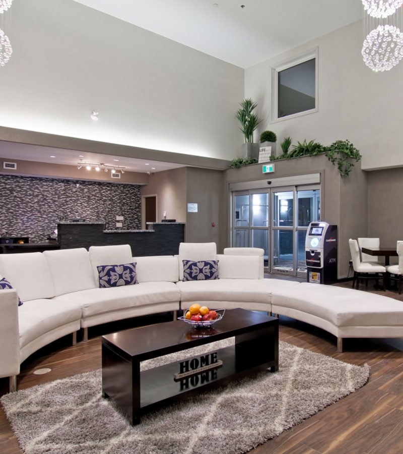 The lobby of the d3h Home Inn & Suites Regina Airport hotel showcases a semi-circular white sectional sofa decorated with white and purple accent pillows and a solid dark wood coffeetable placed over an area rug.  An ATM machine is placed by the glass door entrances while in the background, stands the dark stone check-in counter.