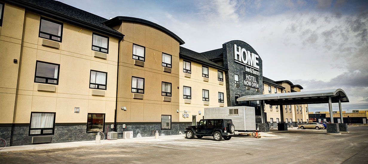 A black banner advertising the opening of the d3h Home Inn & Suites in Swift Current, Alberta, is placed below the hotel's name in bold white lettered signage.  The three storey building is painted in varied tones of cream, light elm brown and charcoal gray with a semi-circular metallic portico (supported by four concrete and metal posts) built over the glass door entrance.