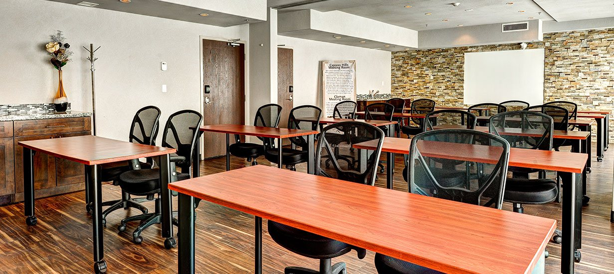 A multi-color stone accent wall, with mounted whiteboard, provides a striking backdrop in the meeting room at d3h Home Inn & Suites Swift Current.  Light red cherry wood writing tables (with two black swivel chairs) are arranged in classroom rows throughout the hardwood floor space.  To the side of the room, a dark wood mahogany cabinet with marbled granite top boasts an accent vase filled with a floral arrangement.