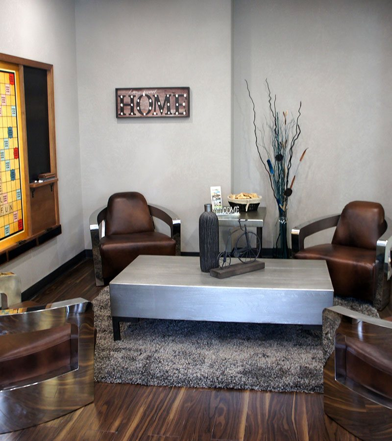 Four chocolate brown leather lounge chairs are placed around a heavy steel top coffee table embellished with decorative knick-knacks in the lounging area at the d3h Home Inn Express Medicine Hat hotel in Alberta.