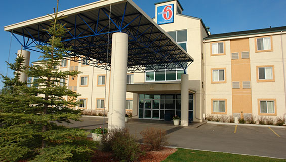 The back entrance to d3h Motel 6 Red Deer, covered over with a rectangular metal portico with concrete post supports.  At the top of the three storey hotel, the corporate logo (a red and bold number 6 against a backdrop of blue), used as signage, overlooks an empty parking lot and Jack pine trees planted in a landscaped area on the property.