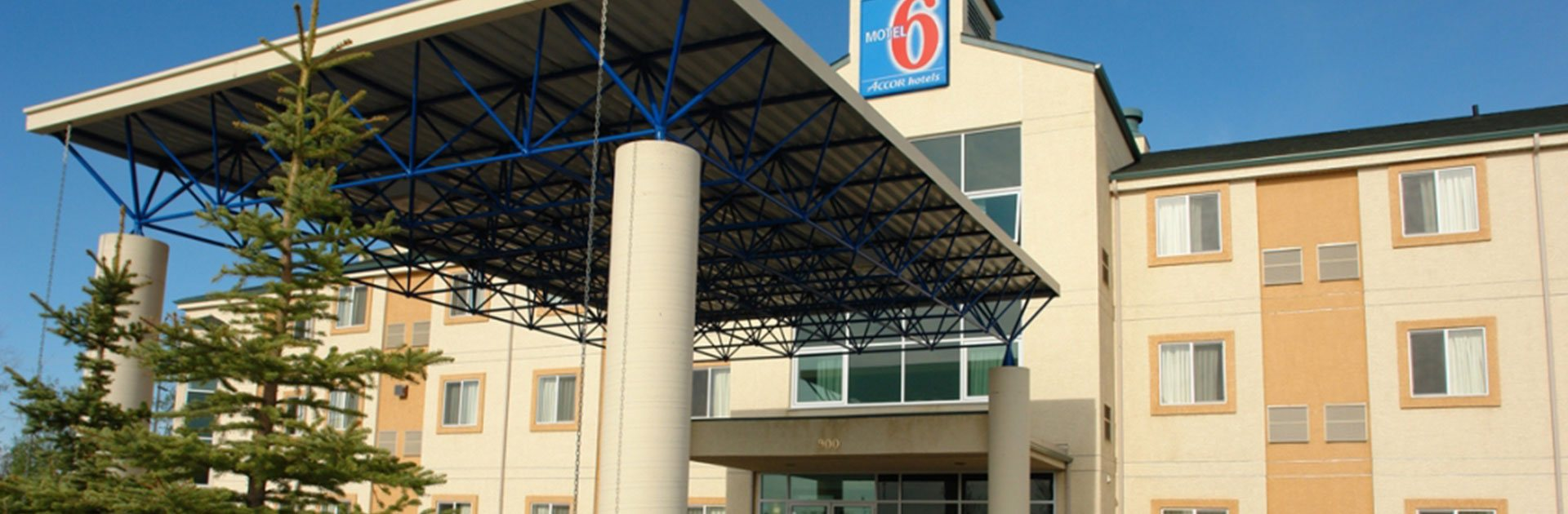 A view of the underside of the steel and concrete portico of d3h Motel 6 in Red Deer, Alberta, covering over the entrance to the three storey building.  The corporate logo (MOTEL in white letter typeset with an oversized 6 in red against a blue background), used as signage, is placed atop the summit of the ivory beige and amber orange two-tone motel.