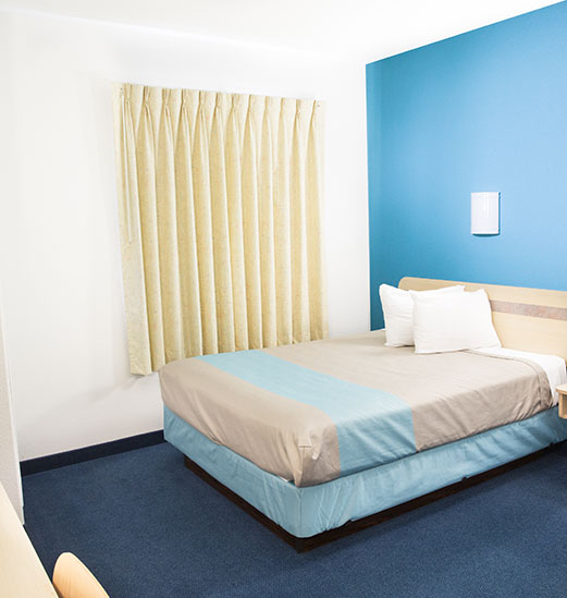 A double sized bed outfitted in horizon gray and powder blue linens, is placed up against a cerulean blue accent wall and is contrasted with the white adjacent wall and ceiling at d3h Motel 6 in Red Deer.  The bed is placed next to a window, completely obscured by pleated parmesan yellow curtains.