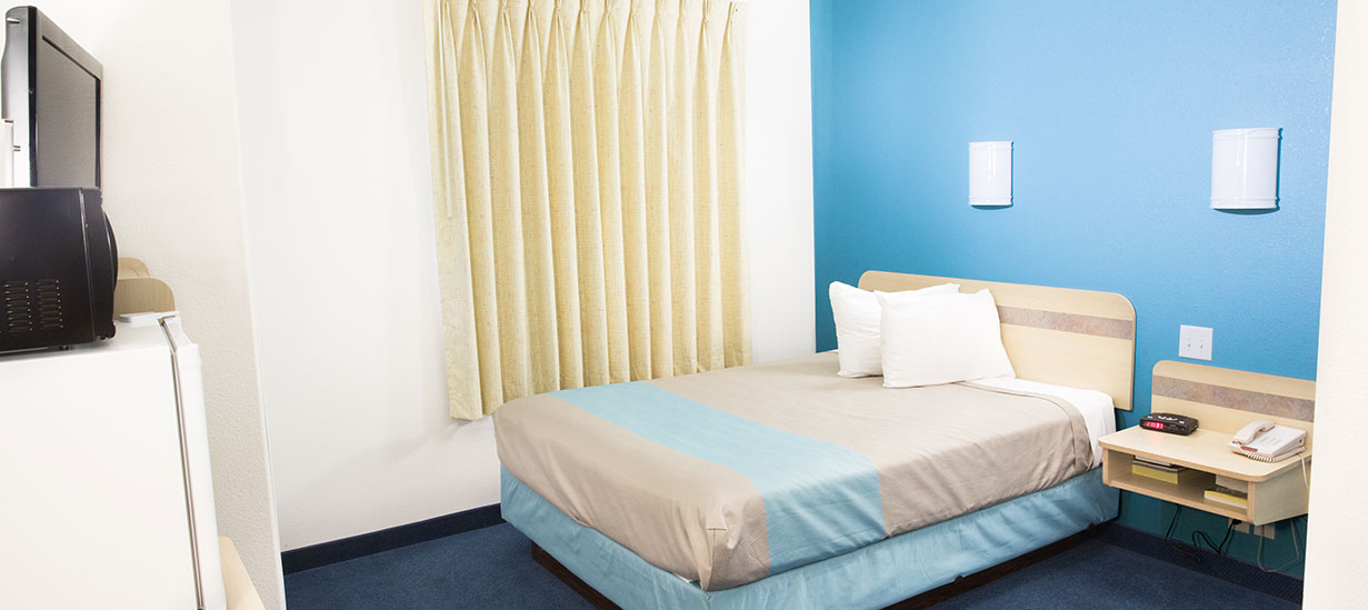 A double bed (dressed in light gray and powder blue linen) featured in a Standard Room at the d3h Motel 6 Red Deer, is placed next to a window completely covered by pale yellow curtains.  In-suite menities include a night stand mounted to the blue accent wall, a 32-inch flatscreen TV, a microwave oven resting on top of the mini-refrigerator.