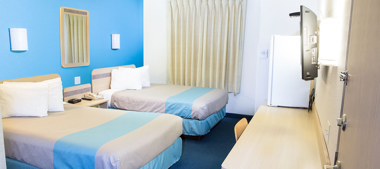 Panoramic view of a two bed suite at d3h Motel 6 Red Deer:  a light wood night stand is placed between double sized beds made up in white, light gray and powder blue linens.  White lighting fixtures and a wood framed mirror are mounted on the cerulean blue accent wall, which the beds are placed up against.  A long light beige color wood table with matching chair and on which sits the in-suite mini fridge, is placed against the wall opposite the beds.  A wall mounted flatscreen TV is also placed directly in the sightline of the beds.