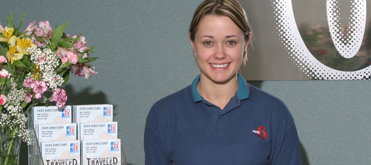 A smiling young blonde female employee at d3h Motel 6 Red Deer is standing next to a display of directories and a vase filled with a multi-color floral arrangement.   She is wearing a blue polo shirt designed with corporate logo elements - a red number 6 and MOTEL in white letter typeset.