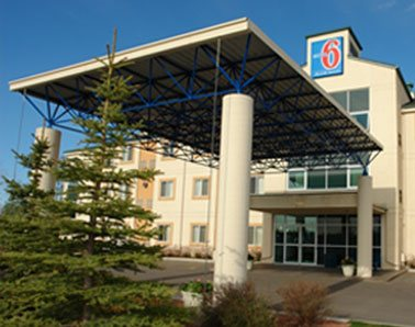 A small view of the glass door entrance to d3h Motel 6 in Red Deer, with two green balsam fir trees placed at the foot of a rectangular portico supported by concrete posts.  The hotel's corporate logo (represented by the number 6 in red bold type contrasted against a blue background) is placed at the summit of the three storey building above the entrance.