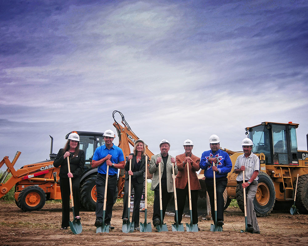 A group of two women and five men from the management team at d3h hotels, wearing construction hard hats, are all holding shovels dug into the dirt of a development site.  Two tractors are seen in the background.