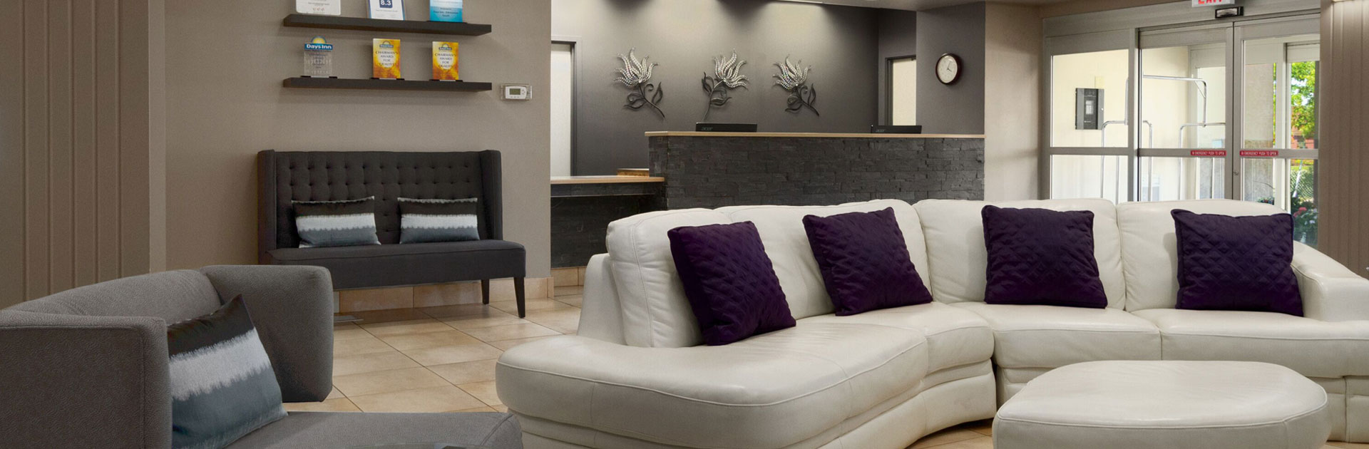 The hotel lobby of d3h Days Inn Edmonton South is furnished with comfortable seating: an elephant gray chair with truncated arms, a charcoal gray loveseat and a two piece plush white sectional sofa (with matching ottoman)  adorned with eggplant purple accent pillows.  The check-in counter is constructed of charcoal gray brick stone, with the matching back wall of the check-in area mounted with three metallic floral art pieces.
