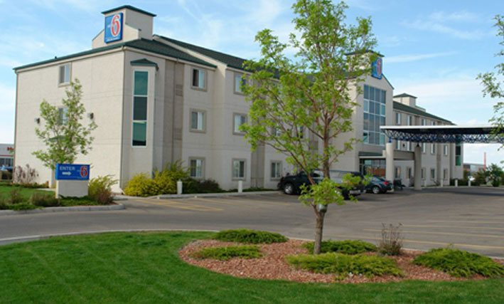 A side view of the parking lot and back entrance to the d3h Motel 6 in Red Deer, Alberta.  In the foreground, a landscaped area features a tree surrounded by manicured lawn space.  Two vehicles are parked next to the concrete and steel portico covering the entrance to the motel.  The corporate logo (in red, white and blue), used as signage, is placed in two locations at the summit of the ivory beige three storey building.