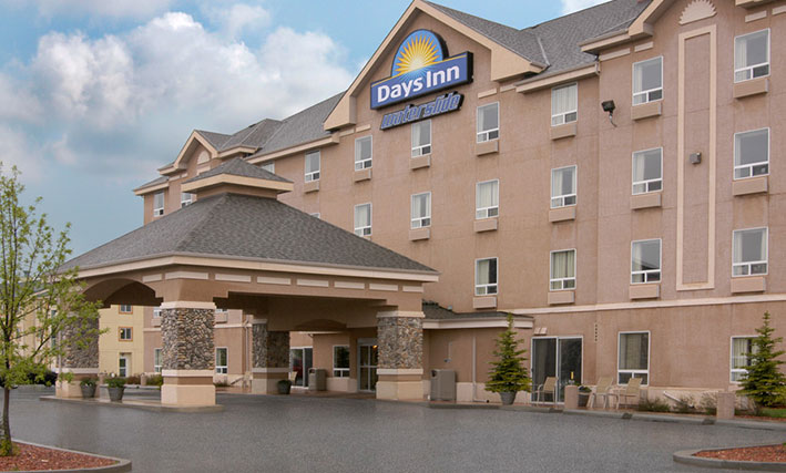 The entrance view of d3h Days Inn Red Deer hotel in Alberta showcases a large square pavilion-shaped portico constructed of concrete and stone.  Placed at the summit of the four storey hotel is the Days Inn corporate sign (represented with a yellow sunrise icon against a blue background), accompanied by lettering signage with waterslide presented in blue and white outline typeset.