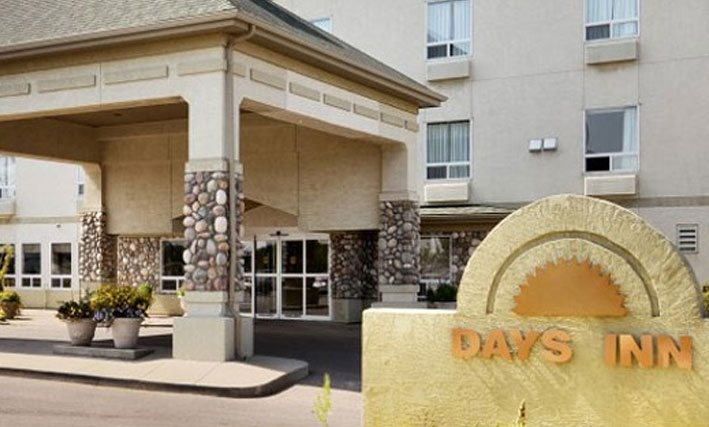A legacy photograph of a d3h Days Inn property in 1999.  The glass front entrance is covered over by a square concrete portico with stone accent trim on the support posts.  Concrete planters bear plants and flowers and a yellow stone monument of a sunset icon of the corporate logo stands in the foreground.