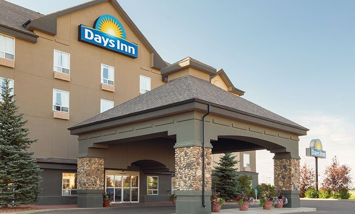 A large pavilion shaped concrete portico structure with stone accents is built over the entrance to the d3h Days Inn Medicine Hat in Alberta.  At the topmost point of the building, the corporate logo (bright yellow sunrise icon and brand name in bold white lettering against a blue background) overlooks the entrance area adorned with terracotta planters of florals and two tall Douglas fir trees planted alongside the portico.