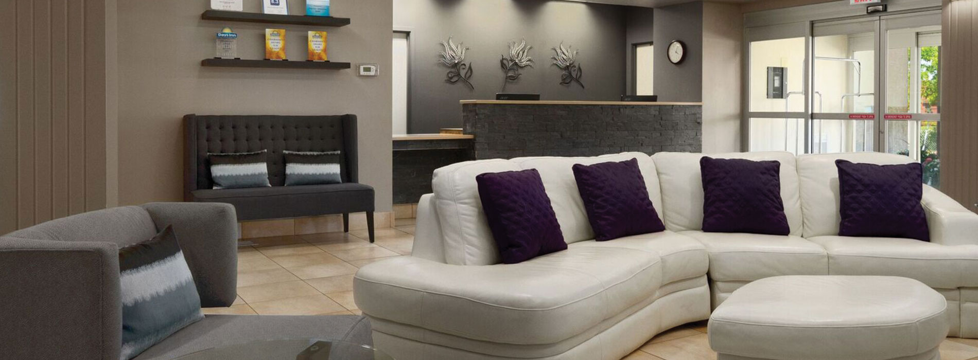 The lobby in d3h Days Inn Edmonton South is a welcoming space with comfortable seating:  a plush white sectional sofa with matching ottoman, a gray single seat armchair and charcoal gray loveseat placed next to the stone check-in counter.  Three silver and black metallic tulip wall ornaments are mounted against the cloudy concrete gray walls behind the check-in desk.