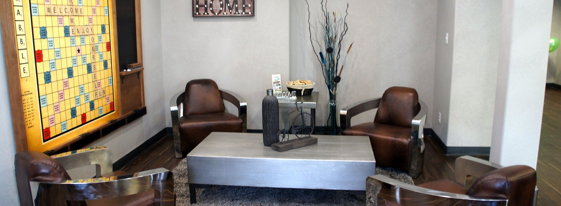 Four leather club chairs with thick metallic arms are matched with a solid metal top coffee table and side end table in the lounge and recreation space of d3h Home Inn Express in Medicine Hat, Alberta.  A large Scrabble board game is mounted against light gray walls with an attached blackboard for score keeping.
