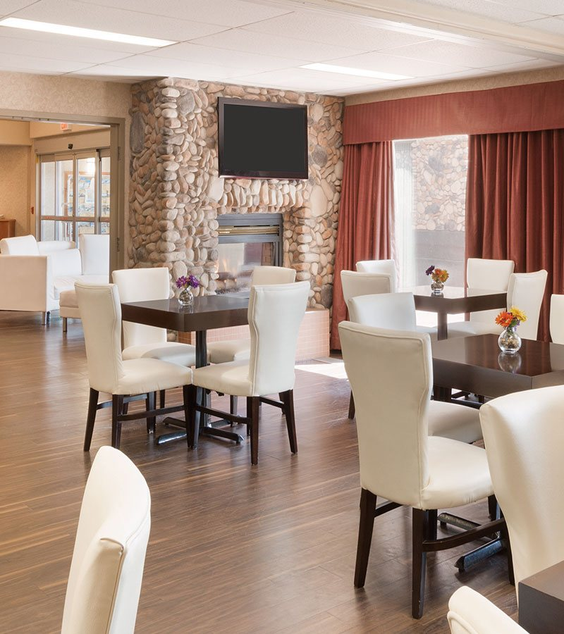 Hardwood floors run through the eating and dining space of d3h Days Inn Red Deer with thick square wood block tables and white high back dining chairs placed next to a large window draped with pleated salmon color curtains and a stone fireplace with mounted flatscreen TV.