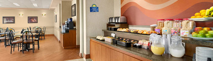 The breakfast counter of the Daybreak Café at d3h Days Inn Red Deer is stocked with trays of baked goods, pitchers of beverages, bowls of fruit, containers of cereal, and condiments.  The breakfast bar overlooks the hardwood floor dining space and the coffee bar in the corner niche.