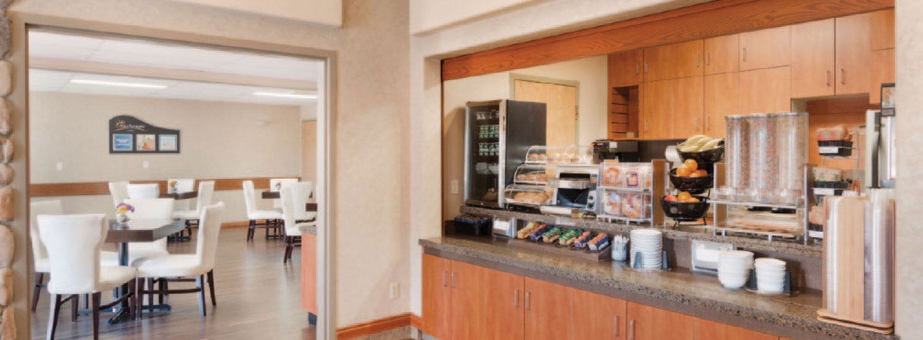 The Daybreak Café at Days Inn Red Deer showcases a long granite top counter with red ochre brown cabinetry.  Bowls of fruit, a mini refrigerator unit, stainless steel toaster, baked goods housed in display cases, and dining ware all sit atop the breakfast bar, which overlooks the entrance to the eating space populated by square tables and white upholstered Parsons chairs.