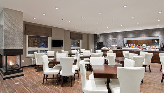 A panoramic view of the HomeEssentials breakfast area at d3h Home Inn & Suites Regina Airport showcases a long granite countertop stocked with food and appliances placed up against a gray stone back wall with a cut out view of the kitchen.  Square chocolate brown eating tables and white upholstered dining chairs are placed throughout the area, with a glass enclosed gas fireplace in the corner.