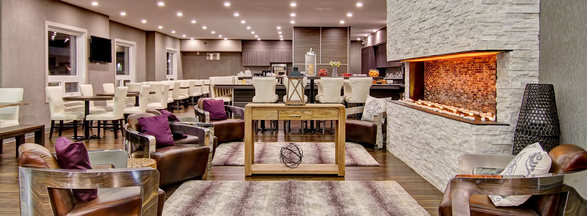 Brown leather club chairs and a tall majestic off-white limestone electric fireplace define the lounge space at d3h Home Inn & Suites Saskatoon South.  Rows of eating tables, benches and wrap-around breakfast counter, all amidst a sea of white upholstered dining chairs, define the HomeEssentials breakfast bar.