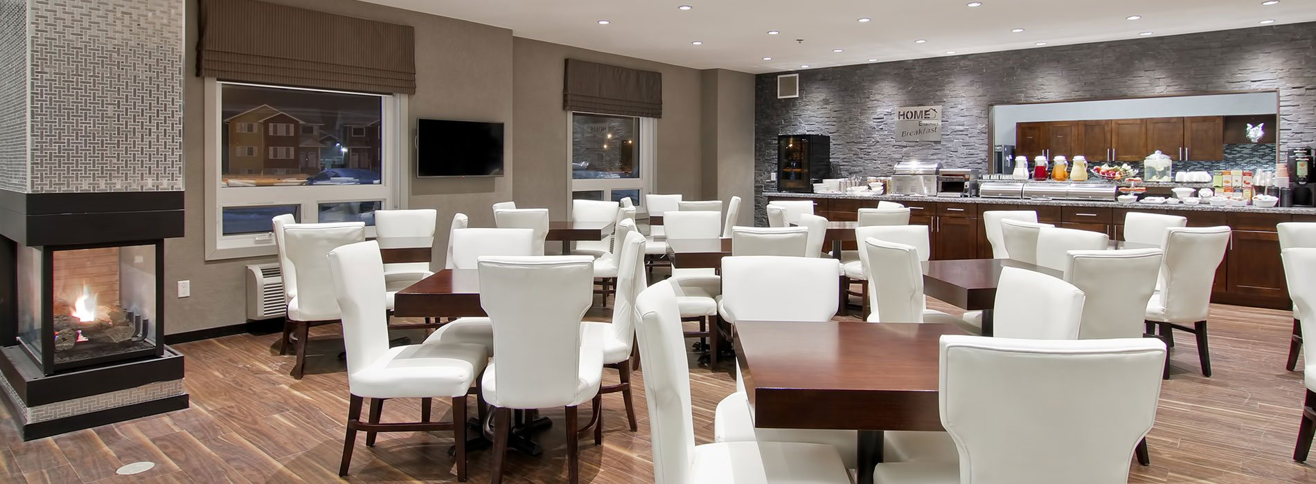 Square chocolate brown eating tables and white high backed upholstered chairs are placed throughout the HomeEssentials breakfast room at d3h Home Inn & Suites Regina Airport.  A long marbled granite top breakfast counter, with chocolate brown cabinetry, (stocked with beverages, stainless steel appliances, eating ware and utensils), is placed up against a fossil gray stone accent wall.  Other amenities include a wall mounted flatscreen TV and a glass enclosed fireplace with silver metal herringbone patterned surround.