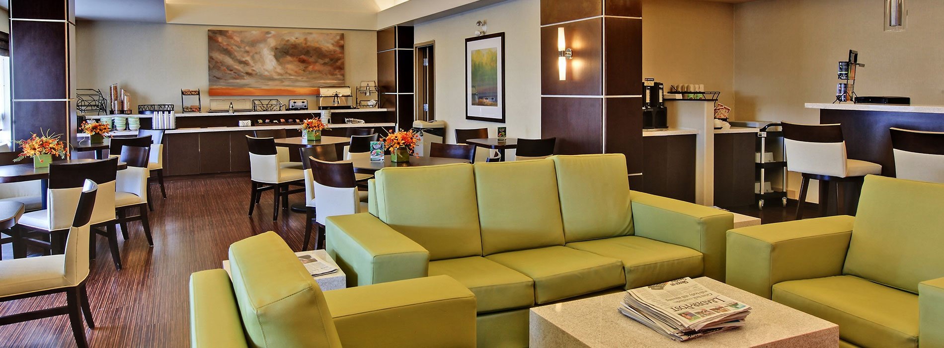 The breakfast and sitting space at d3h Home Inn & Suites Yorkton features wood grain chestnut brown hardwood floors and a long two tiered breakfast counter stocked with dining ware and stainless steel appliances.  Square eating tables and upholstered dining chairs are placed throughout the breakfasting area.  In the sitting area, modern cube shaped coffee and end tables flank a chartreuse green vinyl sofa and armchair set.