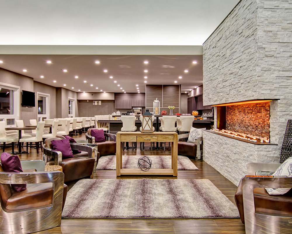 The large white birch limestone electric fireplace provides heating to the lounging and dining area of d3h Home Inn & Suites Saskatoon South.  Leather club chairs with thick metal arms surround the fireplace and a rustic console table.  The woodgrain laminate wall panels of the breakfast bar are seen in the background amidst rows of square eating tables and benches placed amongst a sea of carefully arranged white upholstered dining chairs.