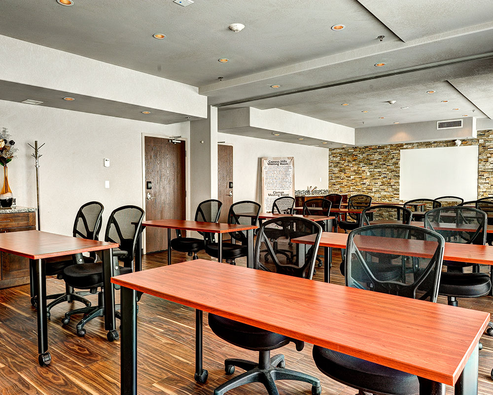 Rows of red cherry wood writing desks, each with a pair of black ergonomic chairs, are placed throughout the hardwood floor space of the meeting room at d3h Home Inn & Suites Regina Airport.  A white board is mounted against a vivid multi-color stacked stone accent wall at the back of the room.