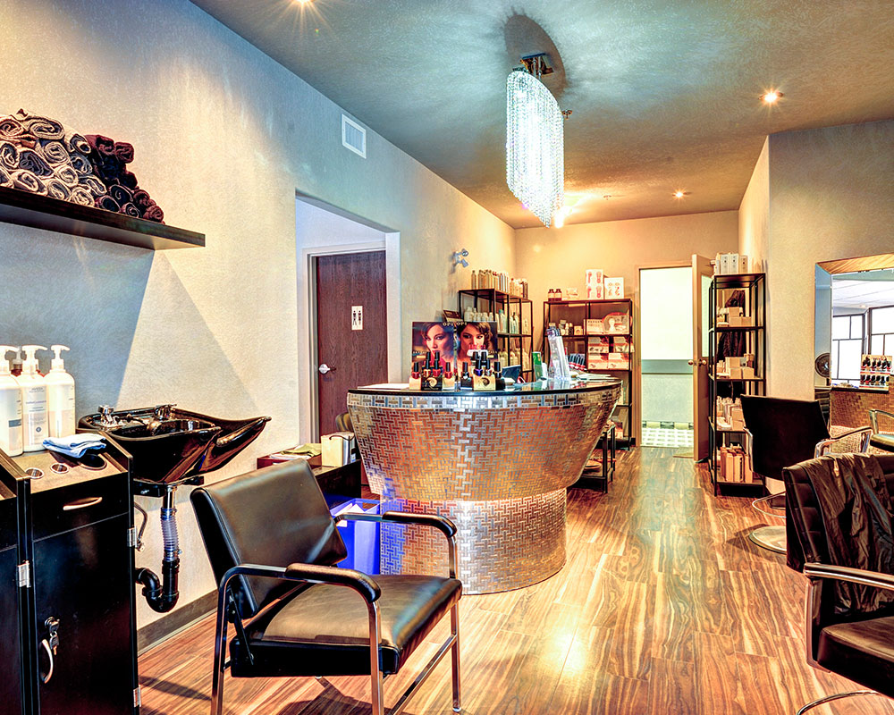 Spa facilities at a d3h managed property.  In the center of the space sits a round silver metallic herringbone patterned reception desk, displaying merchandise and pamphlets.  In the background, three multi-level black metal shelving units display more merchandise for sale, while in the foreground, a black vinyl reclining chair is tucked under a black shampooing basin sink.