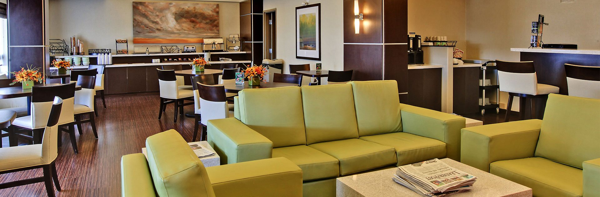 A modern furniture set is featured in the lounge space at d3h Home Inn & Suites Yorkton: a vinyl chartreuse green sofa and armchair set is matched to solid cube shaped coffee and end tables.  A coffee bar is set in a secluded corner next to the breakfast area, while a two-tiered elongated counter, bearing stainless steel appliances and eating ware, is lined up against the back wall of the dining area.  A series of square tables and white upholstered dining chairs are placed throughout the space.