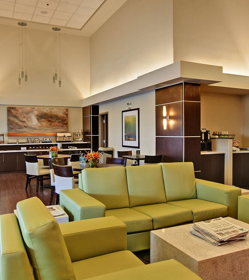 The lounging area of d3h HomeSuites Regina East is furnished with matching chartreuse green vinyl sofa and armchairs and modern solid cube coffee and end tables.  In the background, a long two tiered breakfast bar laden with stainless steel countertop appliances resides against the back wall from which hangs a large painting of a blue sky obscured with dark clouds.  Square eating tables and white upholstered chairs occupy the dining area.