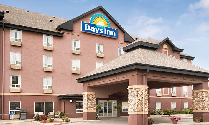 A large square pavilion shaped portico constructed of concrete with stone accents, covers over the glass door entrance to d3h Days Inn Calgary Airport hotel in Alberta.  The Days Inn corporate logo (represented by a yellow sun with a blue background) is placed at the triangular roof summit of the four storey building.  To the side of the entrance, sits a barbecue grill and an outdoor lounge area furnished with patio chairs.