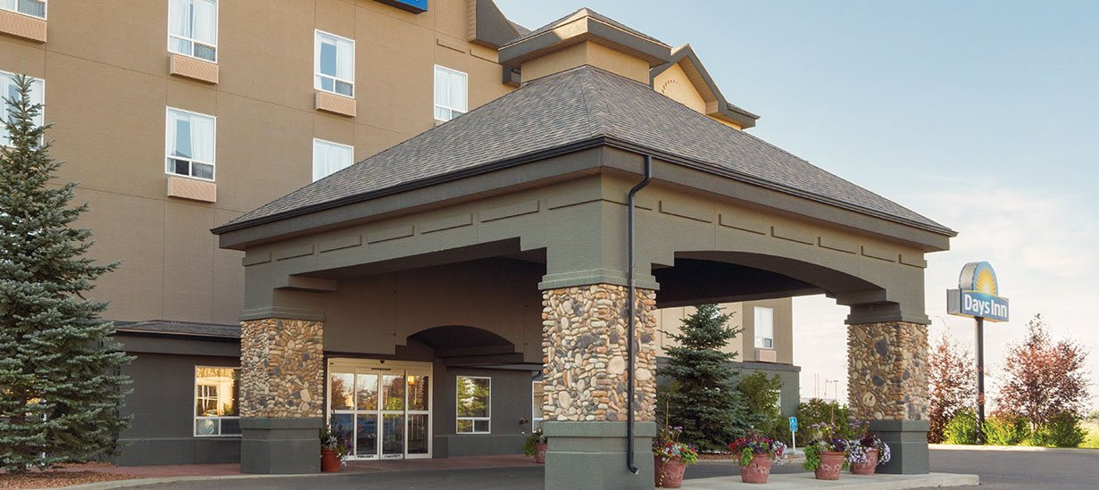 At d3h Days Inn Medicine Hat, the double roof, concrete and stone accent portico provides coverage over the entrance to the hotel.  Two tall majestic Jack pine trees stand on bilateral sides of the entryway, while adobe planters filled with florals are placed throughout the covered space.