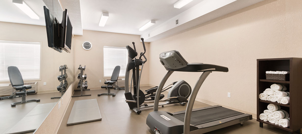 The fitness centre at d3h Days Inn Medicine Hat is fully equipped with modern amenities such as a treadmill, elliptical trainer, and a weight bench accompanying a rack of free weights.  A wall mirror stretches across the length of the gym with a flatscreen TV mounted high up on the mirror's surface.  Other amenities include a multi-level shelf stocked with fresh linen and towels.