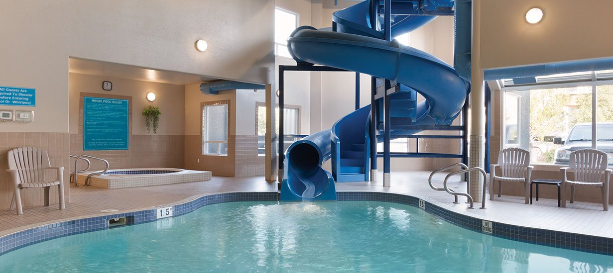 The bright indoor pool area at d3h Days Inn Medicine Hat showcases a large twisting blue waterslide that slithers into a blue tiled swimming pool.  In a secluded corner of the pool area, a round whirlpool sits facing a window, while white patio chairs are placed around the perimeter of the pool area.