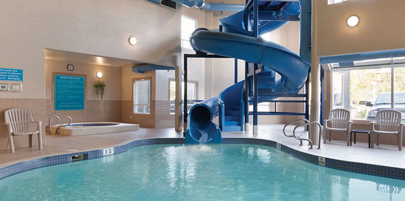 The winding blue plastic waterslide slithers into an oasis shaped indoor swimming pool at d3h Days Inn Medicine Hat, with white patio chairs placed at the pool's edge.  Windows in the corner of the pool area provide a pleasant ambience by a round hot tub, while a large picture window overlooking the swimming pool reveals a view of the hotel parking lot.