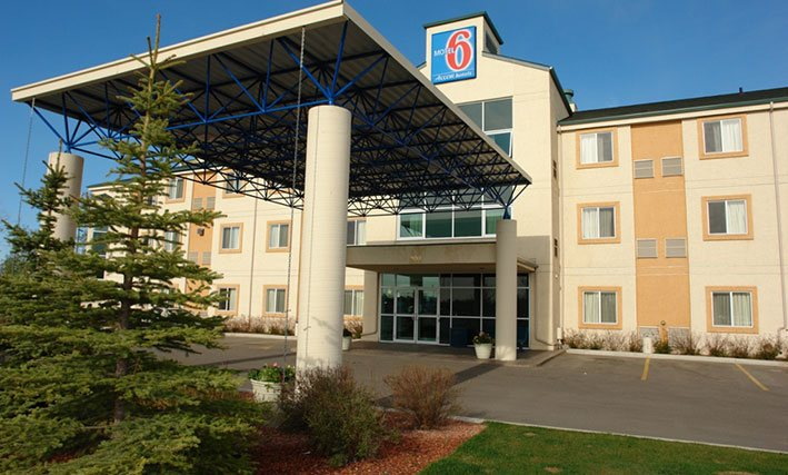 The parking lot entrance to d3h Motel 6 Red Deer features a concrete and steel portico with support posts providing coverage over the glass entrance to the three storey hotel.  Attached to the rooftop summit of the two-tone pastel yellow and latte building, the squared shaped Motel 6 logo (with red and white typeset against a blue background) is used as signage.
