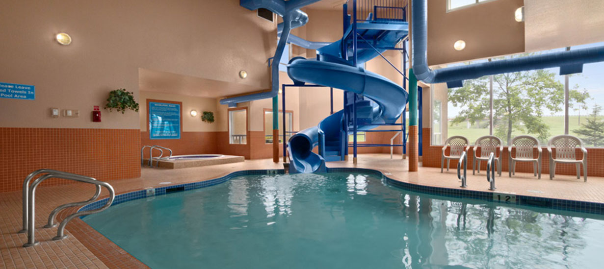 The indoor pool area of d3h Days Inn Red Deer showcases the blue large twisting waterslide snaking into the aqua blue waters of the swimming pool.  The whirlpool is placed in a recessed corner, while four patio chairs line the edge of the pool with the backdrop scenery of green grass and trees seen through a large picture window.