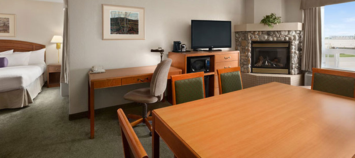 The workspace in the Business Class Suite at d3h Days Inn Red Deer is equipped with matching honey beige wood writing desk (with oatmeal colored upholstered swivel chair), large square work table (with wood chairs upholstered in green) and a shelving unit bearing a flatscreen TV, microwave, coffeemaker and mini-refrigerator.  In the corner, a stone glass-enclosed fireplace sits next to a window dressed in khaki drapery.