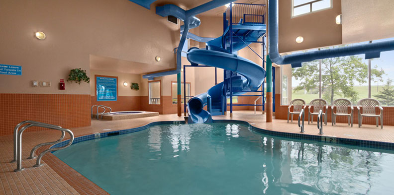 A large blue twisting waterslide slithers into the indoor swimming pool at the d3h Days Inn Red Deer hotel.  The interior of the pool area is defined by two-tone sepia color walls and burnt umber brick accents.  A whirlpool is placed in a secluded corner, while four white patio chairs are placed by the edge of the pool for spectators.