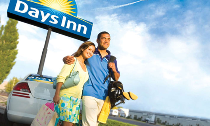 A photo of a happy young couple, the female carrying shopping bags and the male with golf clubs slung over his shoulder, stand before a parked white car and the Days Inn corporate sign (represented by a bright yellow sunrise icon against a blue background with the corporate name in white typeset), making their way to their booked suite.