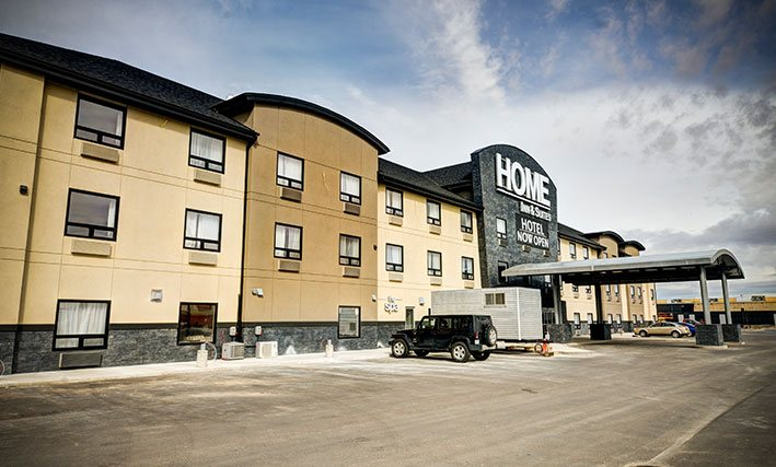 The view of the parking lot of the d3h Home Inn & Suites Swift Current hotel on a clear day, with several vehicles parked next to the semi-circular metal portico covering over the entrance.  The corporate name (in large white lettering) is placed above the entrance, with a black banner advertising Hotel Now Open in bold white lettering typeset.